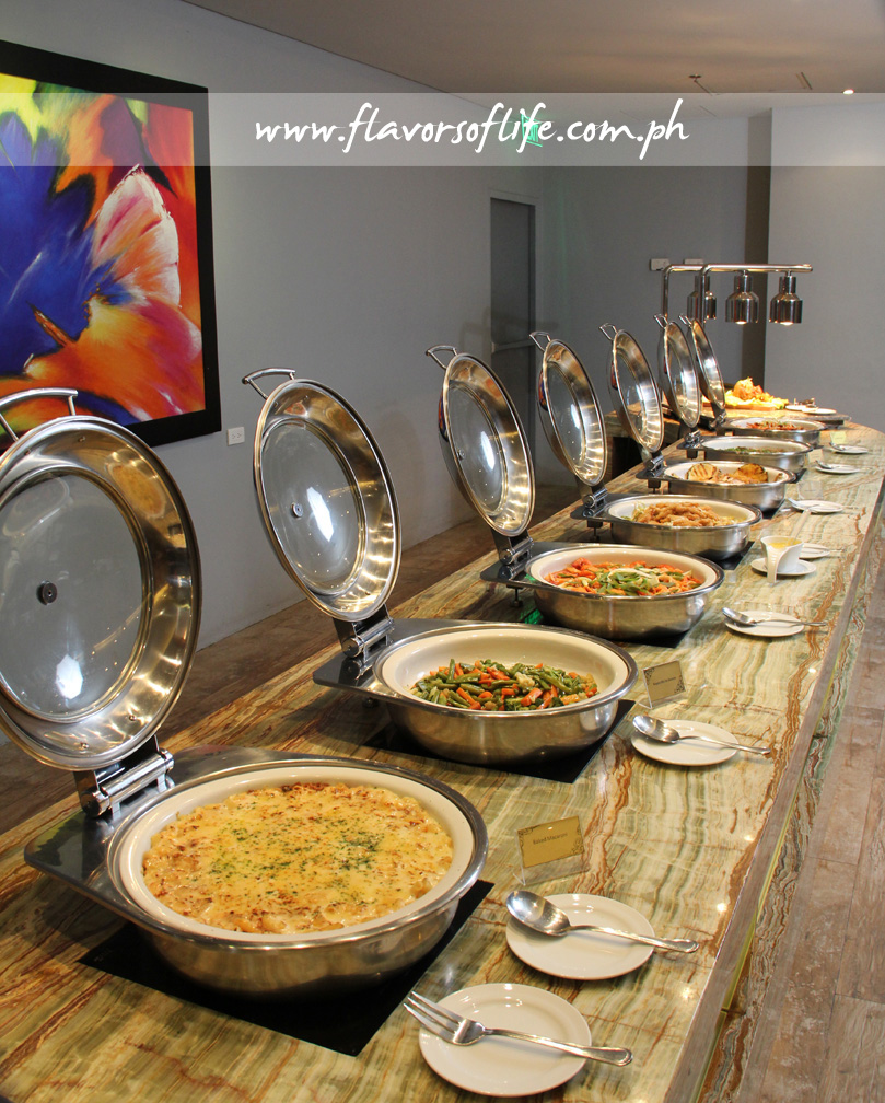 Hot dishes in chafing dishes for the dinner buffet spread of Garden Café