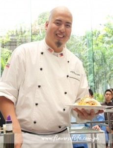 Chef Bruce Lim holding up the platter of Lobster Palabok he whipped up for the demo