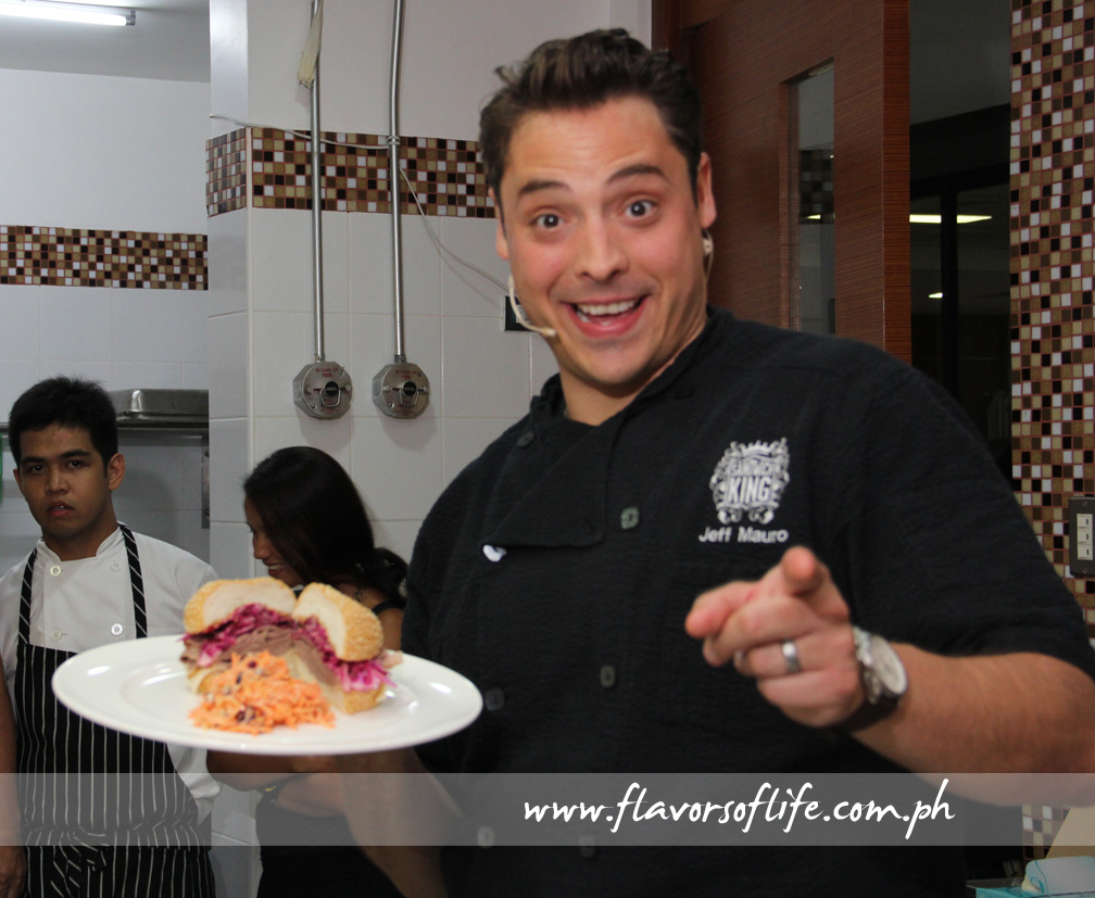 Sandwich King Jeff Mauro holds up his platter of Jewish Brisket Sandwich with Smoked Mozzarella and Red Cabbage Slaw with Carrot and Cranberry Salad on the side