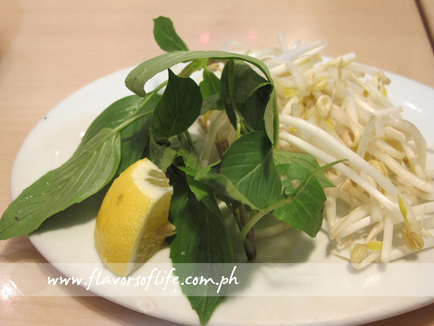 Plate of Vietnamese basil leaves, bean sprouts and lemon wedge that accompanies a pho order