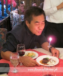 Raff blowing the candle on his birthday pudding