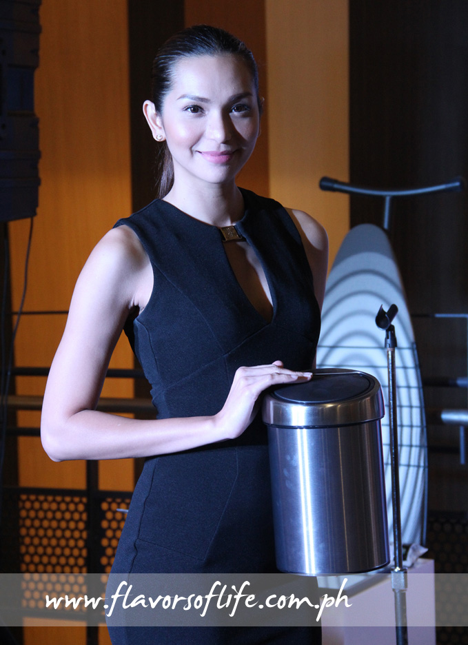 Model holding up a small version of Brabantia's classic pedal bin