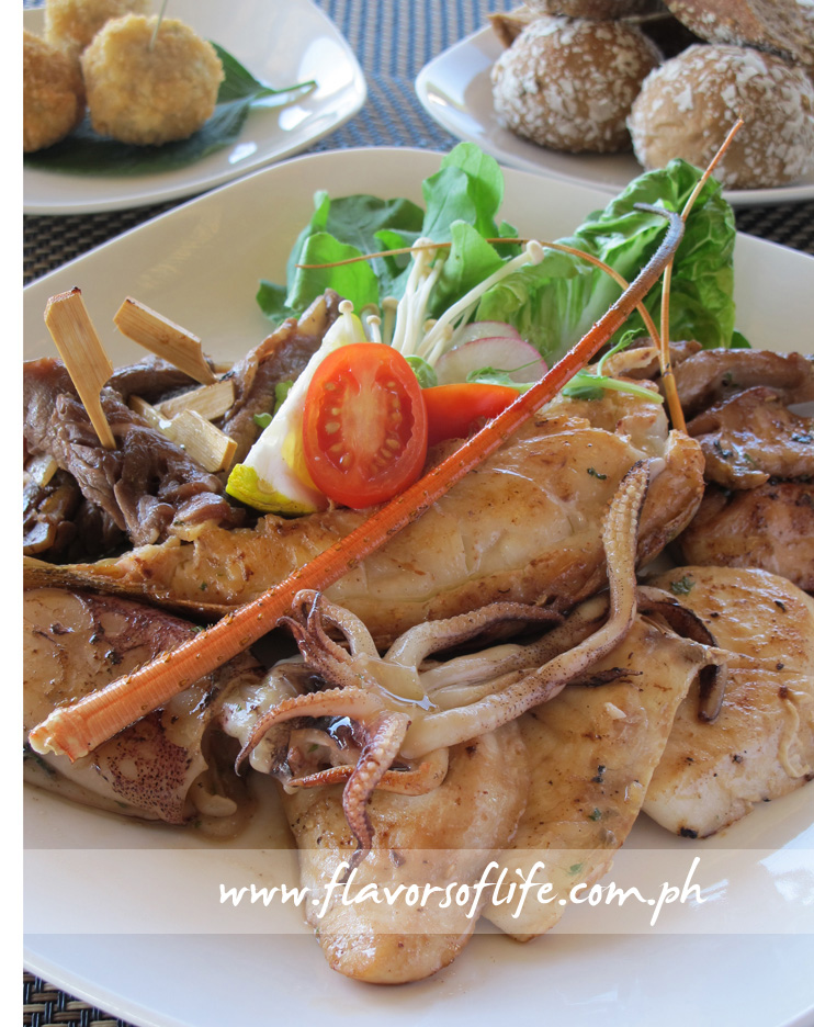 Platter of grilled seafood surrounded by potato-based sides