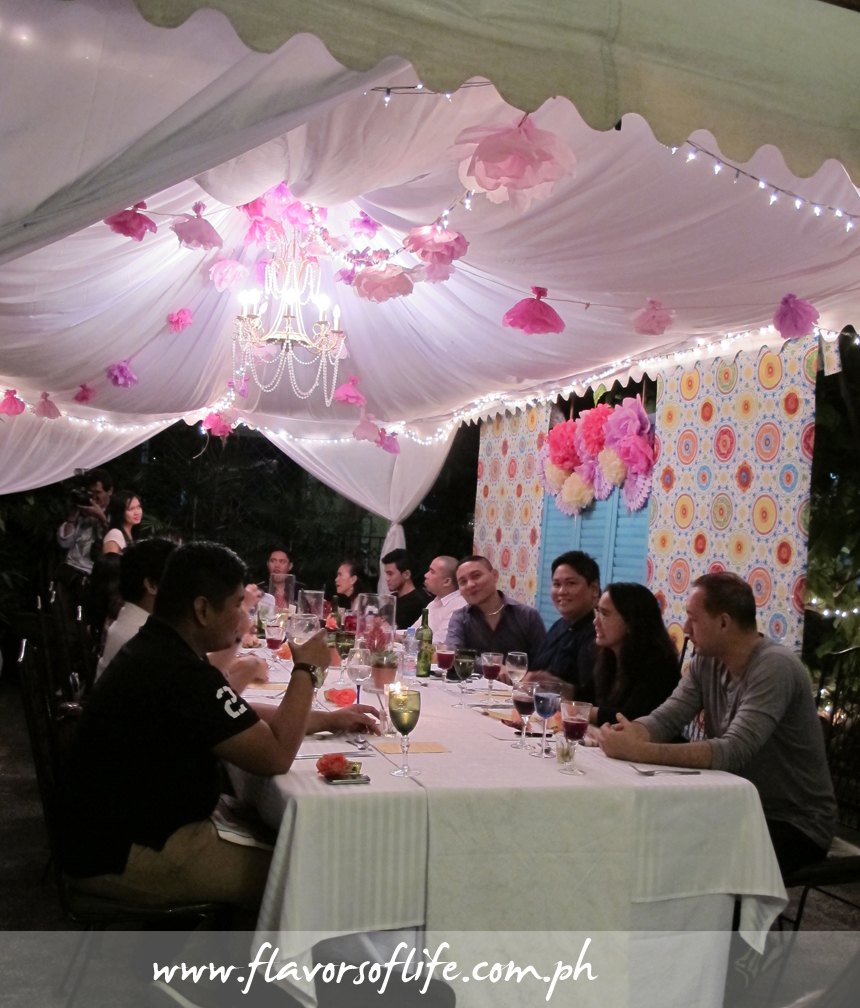 A long table was set in the garden of Tina's Table, under a canopy tent