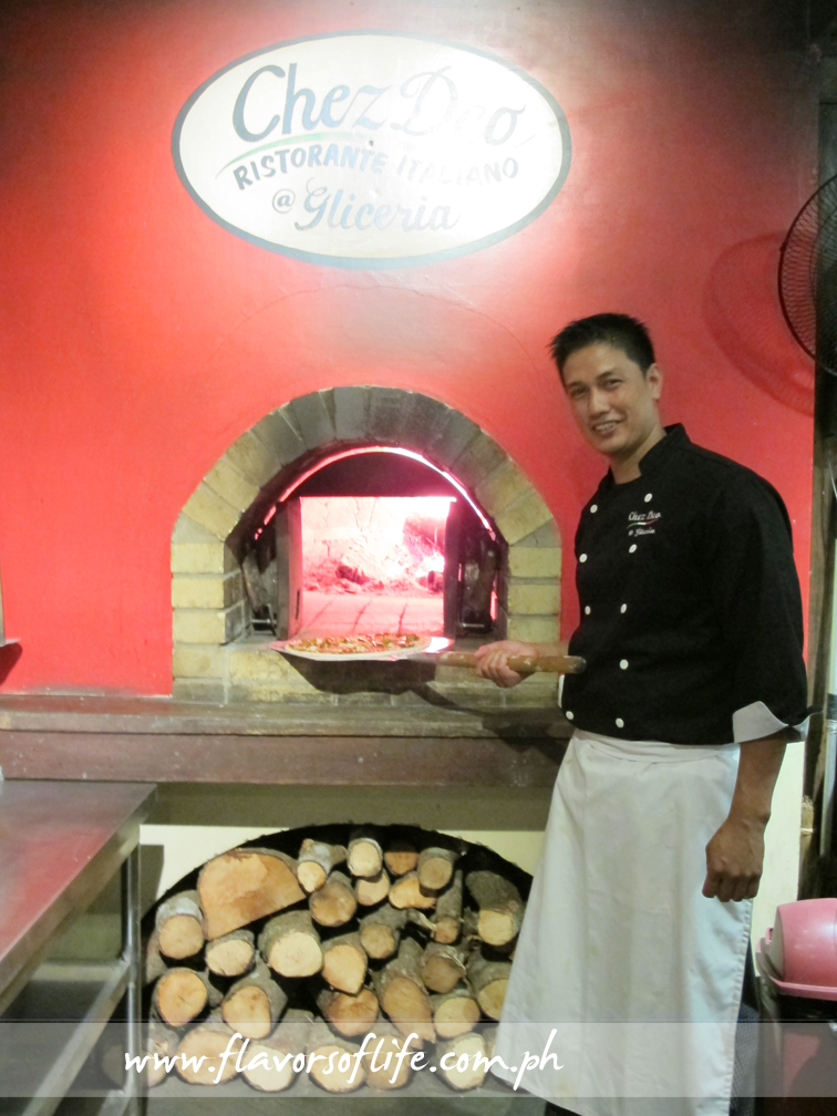 Chef Deo de Castro places a freshly kneaded and topped artisan pizza in the brick oven