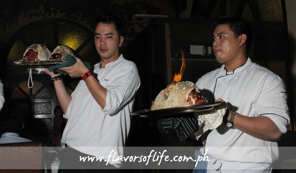 Platters of flaming salt-crusted lapu-lapu being presented