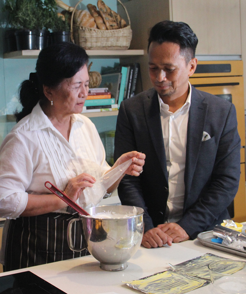 Chef Sau assisting Atching Lillian Borromeo as she made the meringue for the Brazo de Mais during the cooking demo