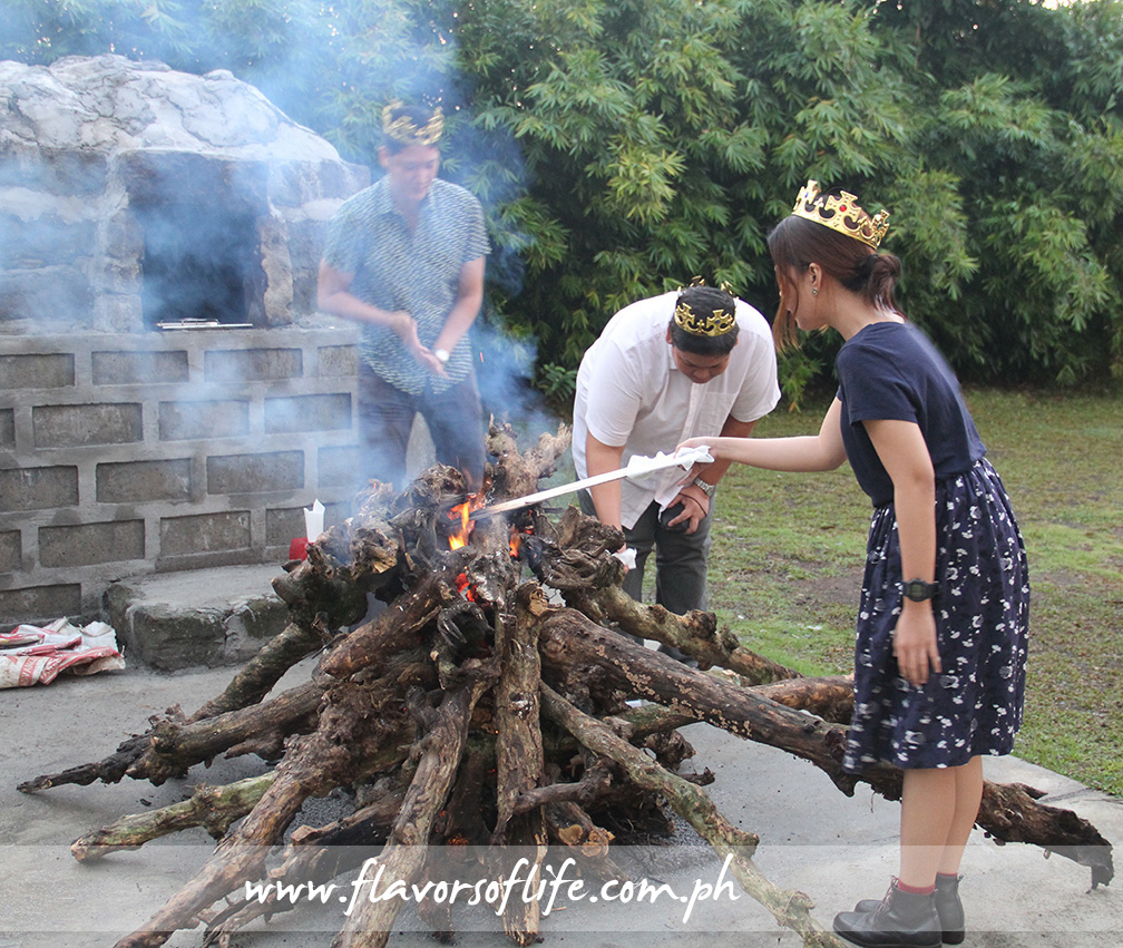 The kings and queen of the event lead in the burning of the log