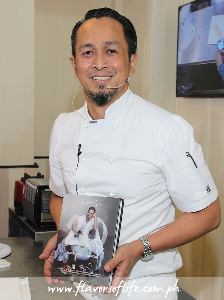 Chef Sau Del Rosario holding up his cookbook