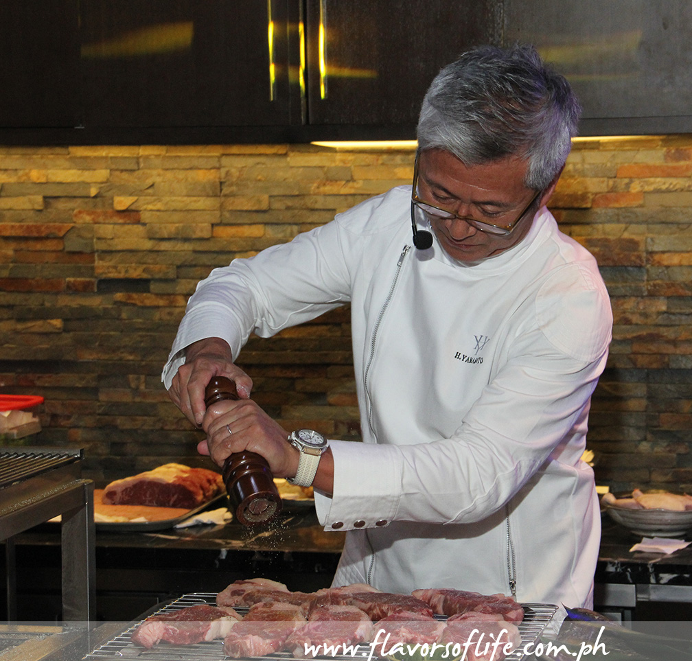 In a cooking demo, Chef Hide Yamamoto shows how to prepare U.S. Black Angus Steak. Cut the steak into 1-inch thick slices, season with salt and pepper, grill over charcoal fire for 1-1/2 minutes per side, then rest for 5 minutes in a 50 to 60 degree C environment for 5 minutes before slicing and serving