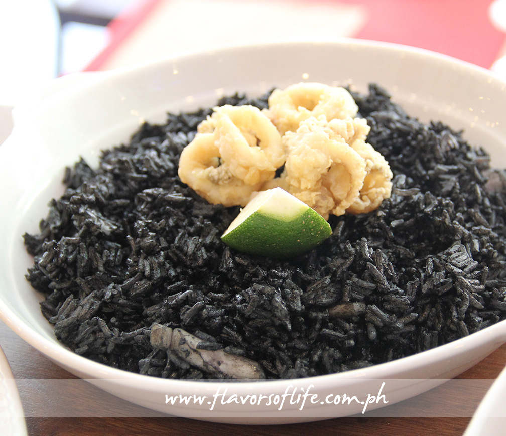 'Paella Nero con Frito Misto' is black ink paella topped with calamari and fried shrimps