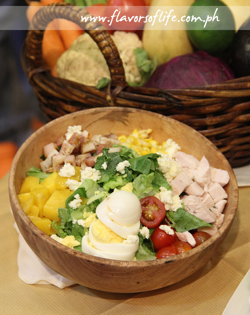 Green Pastures' Farmhouse Salad consists of shredded kale, chopped Romaine, roasted chicken, mambo goat cheese, hard-boiled eggs, bacon, corn, ripe mangoes, grapes and tomatoes