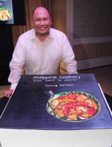 Chef Myke 'Tatung' Sarthou standing before the cake version of his book's cover