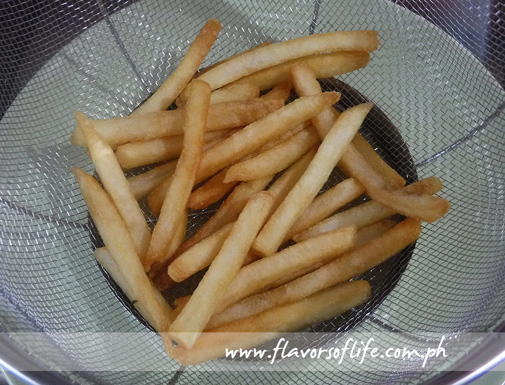 Drain the cooked fries off excess oil on a strainer lined underneath with paper towel