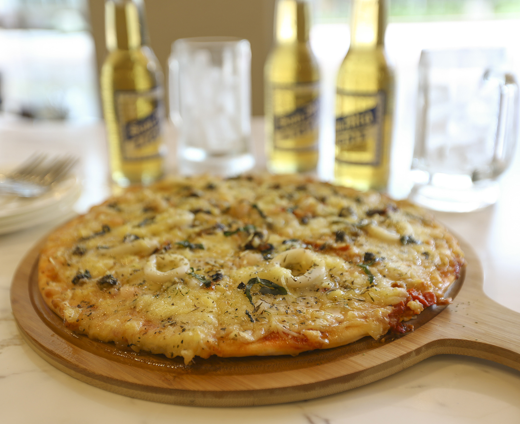 Pizza Pescatora + three bottles of local beer is one of the afforable bar chow and drink Pair & Square combos offered by the restobar