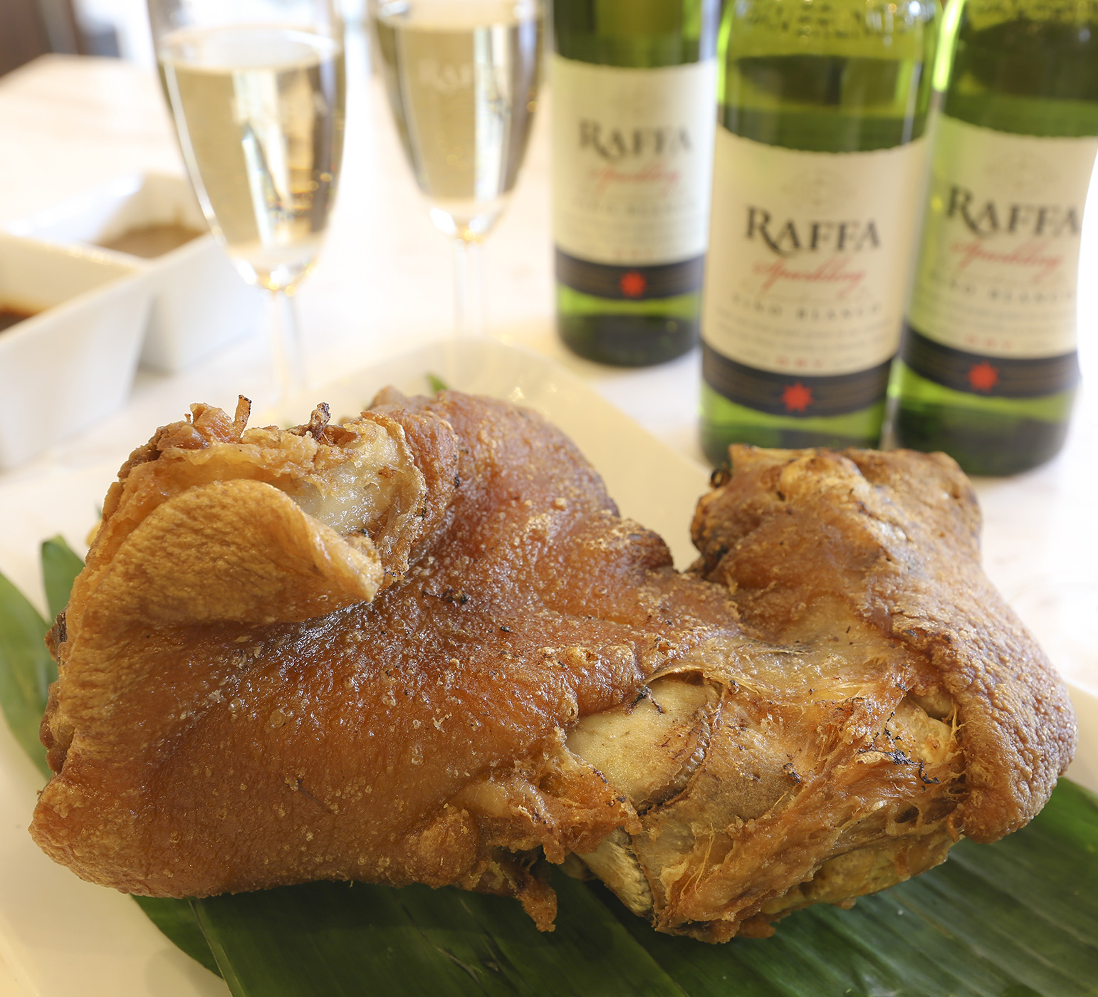 The 'Pair and Square' combination of Classic Crispy Pata and three bottles of Raffa Sparkling Wine